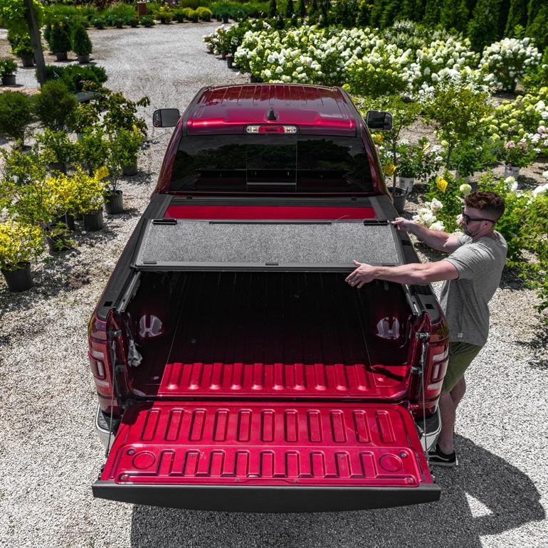 Man putting a trunk hood back in a truck