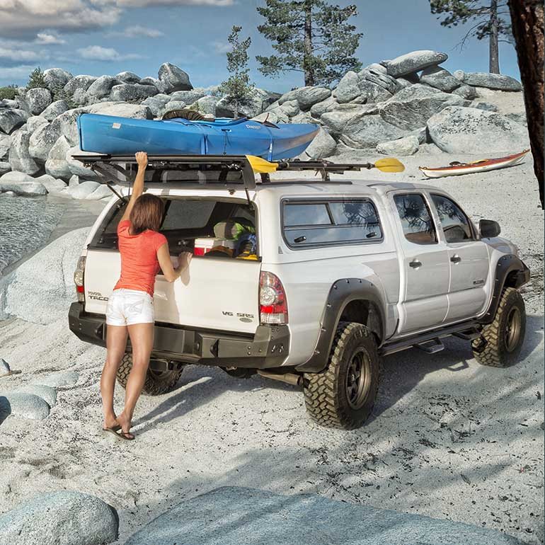 A women unpacking from a white truck by a the beach